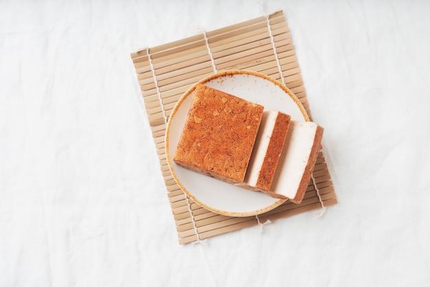 有機燻製豆腐チーズのレンガを竹マットの上に白いプレートで添えました。フラットレイ。上面図。ビーガンスナックのコンセプト
