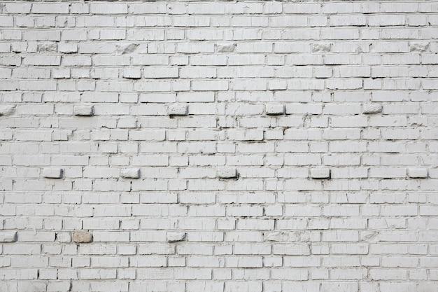Кирпичная старая стена окрашена белой краской