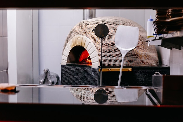 Brick oven with fire for making italian pizza in the kitchen.