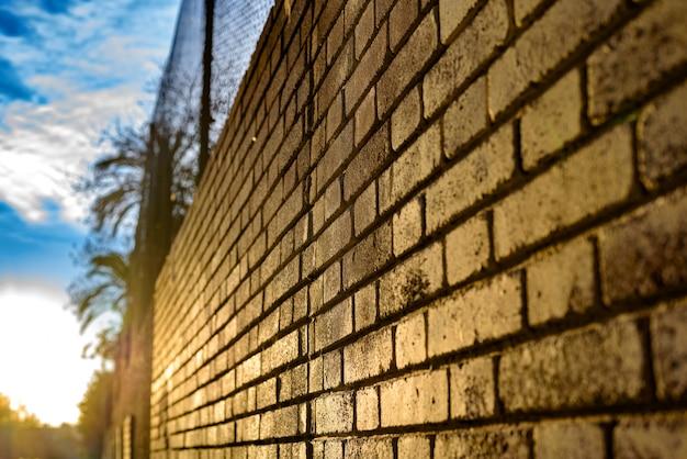 太陽光線と夕暮れ時のレンガ壁の背景