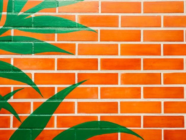 녹색 잎을 가진 벽돌 벽 배경을 그렸습니다. 생생한 컬러 벽돌 벽 텍스처에 빈 공간입니다.
