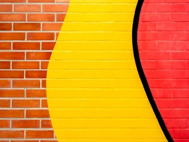 Предпосылка кирпичной стены с желтой и красной краской. пустое пространство на яркой цветной кирпичной стене текстуры.