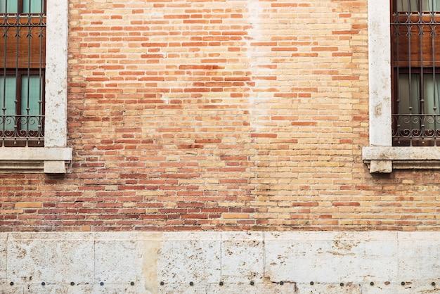 Кирпичная стена между двумя старыми окнами с копией пространства