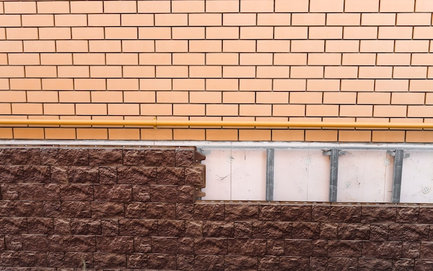 Brick wall and masonry applied to the facade of a building house construction