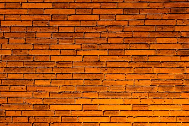 오렌지 백라이트와 표면의 벽돌 벽입니다.