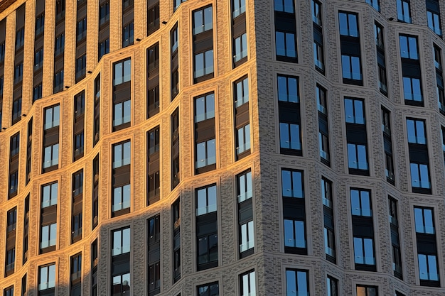 Brick wall of a skyscraper with windows. left illuminated by sunset, right in the shade
