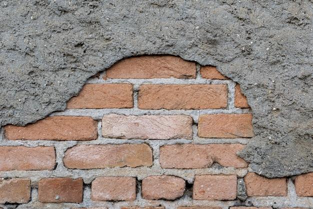 壊れたセメントパテとレンガの壁