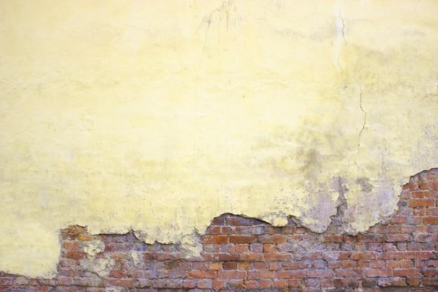 Кирпичная стена с поврежденной штукатуркой