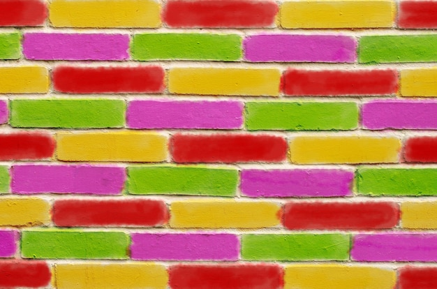 Brick wall, with green purple red and yellow painted bricks.