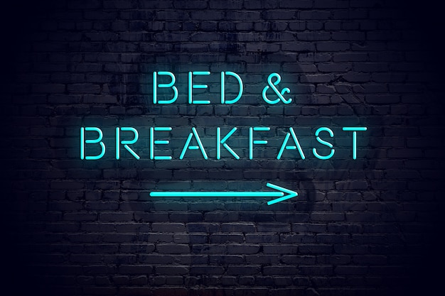 Brick wall with neon arrow and sign bed breakfast