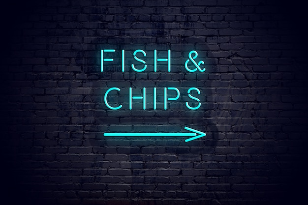 Brick wall with neon arrow and sign fish chips.