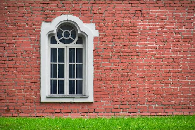Кирпичная стена с одним окном. дом перед фасадом старого здания и зеленым лугом.