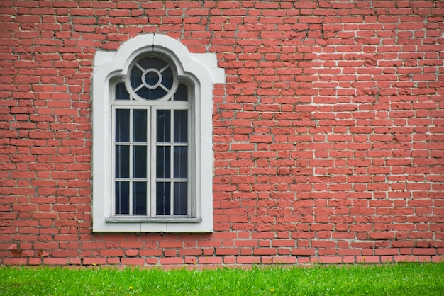 Brick wall with only one window house front facade of old building and green meadow