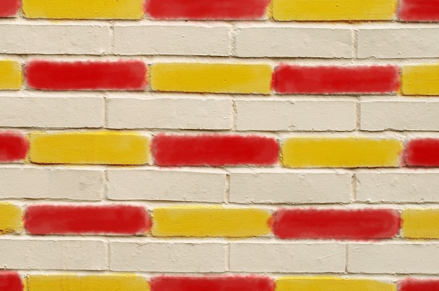 Brick wall, with red and yellow painted bricks.