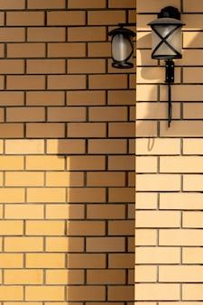 두 개의 가로등과 그림자가 있는 벽돌 벽