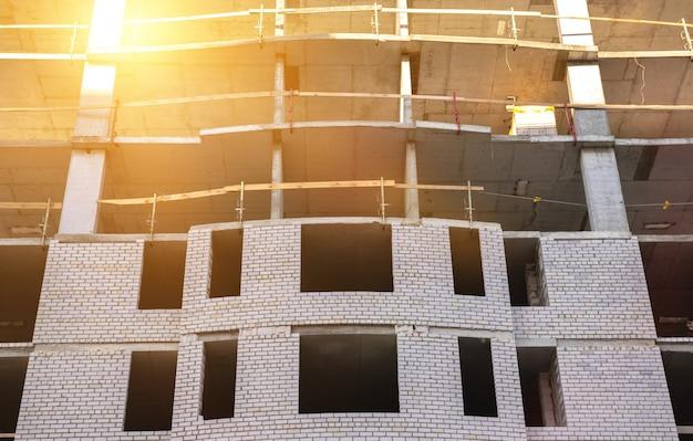 新しい高層住宅の建設現場のレンガの壁。業界ビジネスの背景写真