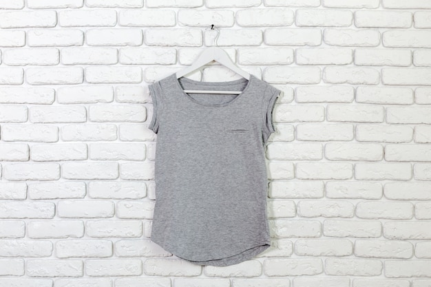 Brick whitewashed wall with t-shirt on hanger