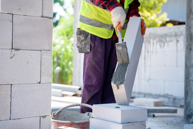 시멘트 모르타르를 사용하여 경량 벽돌을 넣는 벽돌공 빌더. 건설 현장에서