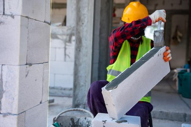 Каменщик-строитель работает в автоклаве из газобетонных блоков с липкой штукатуркой. обшивка стен, установка кирпича при незавершенном строительстве домов, инженерные и строительные концепции. Premium Фотографии