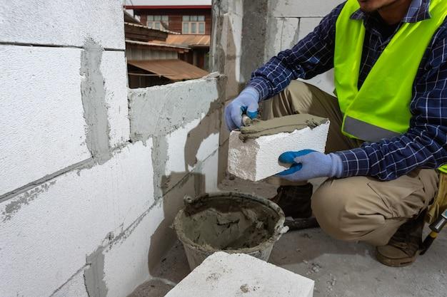 オートクレーブ処理された気泡コンクリートブロックで作業する煉瓦工ビルダー。壁、建設現場でのレンガの設置、エンジニアリングおよび建設のコンセプト。