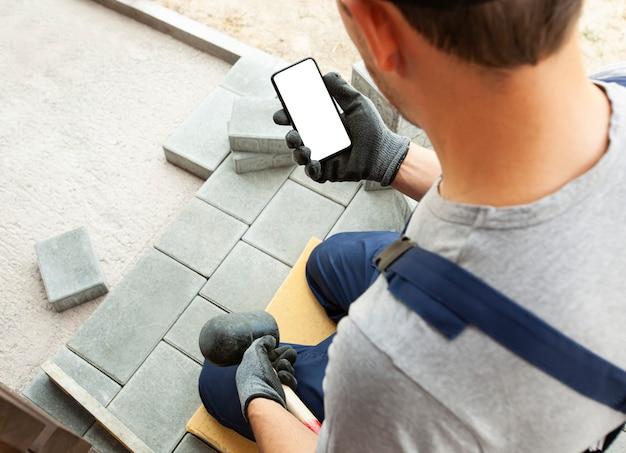 Каменщик держит телефон с пустым экраном в руке на перчатках. макет для ремонта или строительства дома