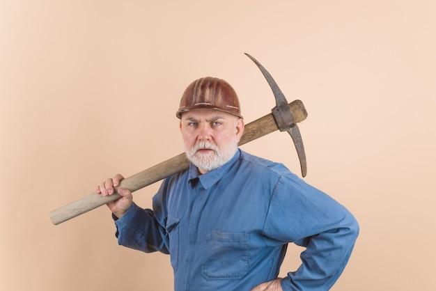 Каменщик в каске с киркой. строитель держит кирку. подрядчик человек с топором. рабочий с киркой. строитель с киркой. мужской рабочий со строительными инструментами.