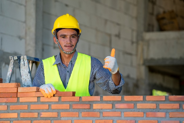 Bricklayer industrial worker installing brick masonry on exterior wall at new house.