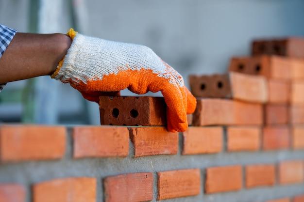Рабочий каменщика промышленный устанавливая кирпичную кладку на внешней стене на новом доме.