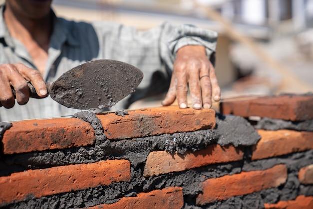建設現場でこてパテナイフでレンガ積みをインストールする職人工業労働者 Premium写真