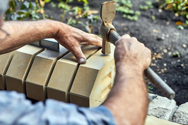 망치를 사용하여 마주 보는 벽돌에서 새 울타리에 벽돌을 설치하는 벽돌공