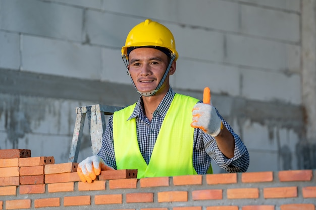 Bricklayer laying bricks to make a wall at construction site.