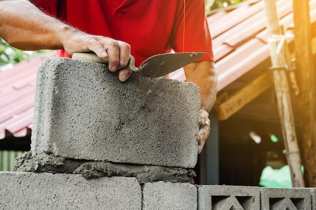 Каменщик человек работает построить для строительства дома
