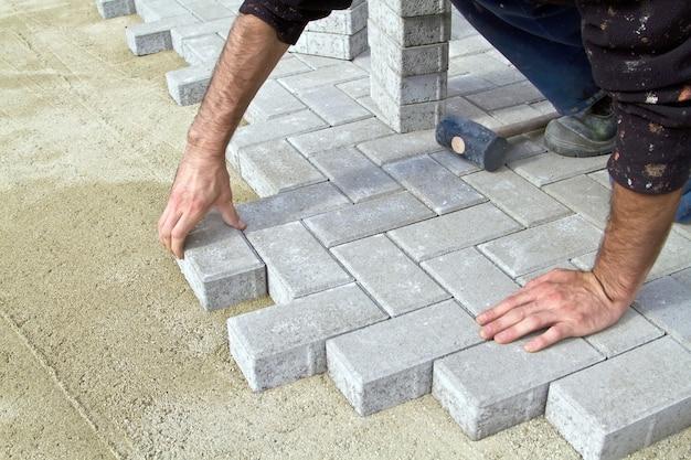 Каменщик на тротуаре экономит плитку.