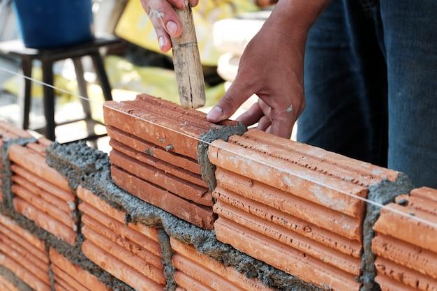 Bricklayer worker installing brick masonry on exterior wall.