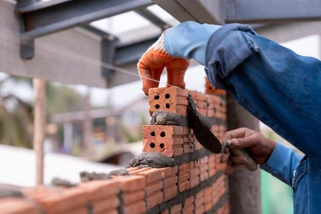 건설 현장에 흙 퍼티 나이프로 벽에 벽돌 벽돌을 설치하는 벽돌공 작업자