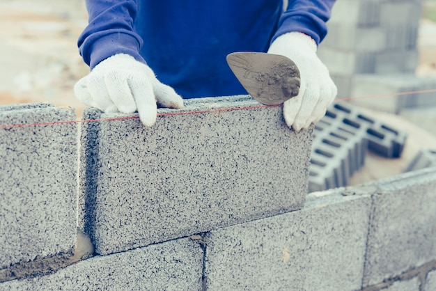 Bricklayer worker installing brick masonry.