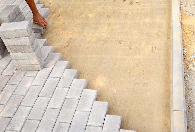 벽돌공 손은 보도를 놓는 준비된 모래 혼합물 과정에서 포장 석판을 낳는다