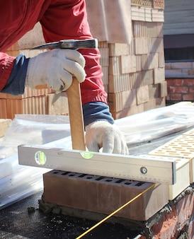 煉瓦工は、基礎に新しい家の壁をレンガ積みの石積みのこてで手渡します。レンガを設置する産業用煉瓦工のクローズアップ。煉瓦と建物の壁を扱う煉瓦工と石工。