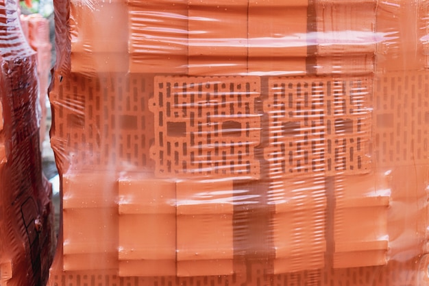 건설 현장의 팔레트에 있는 벽돌. 건축 자재. 집을 짓기 위한 붉은 벽돌. 셀로판 필름으로 덮인 벽돌 포장.