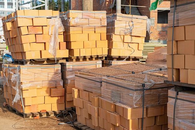 Кирпичи в поддонах на строительной площадке. строительные материалы. красный кирпич для строительства дома.