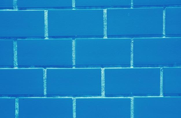背景の鮮やかな青色のレンガの壁