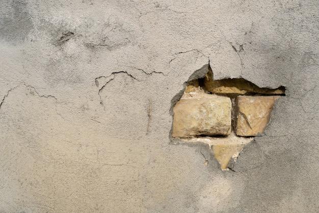 灰色の壁の漆喰の穴からレンガが見えます。抽象的な背景