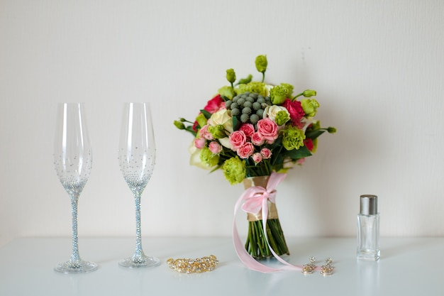 Bridal beautiful romantic bouquet of various flowers, glasses for champagne, in brilliant stones, a gold hairpin, earrings. selective focus.