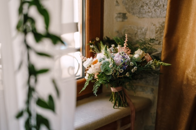 Bridal bouquet of cream roses pink peonies eustoma waxflower astilbe limonium branches of eucalypt