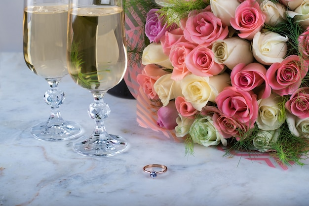 A bridal bouquet of delicate roses and ring with a diamond two glasses of champagne fore wedding valentine's day