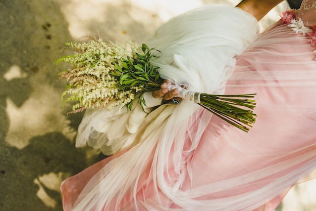 Bridal bouquet held by her with her hands at her wedding