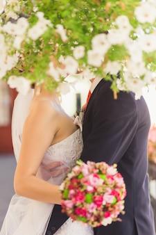 Букет невесты в руках поцелуи жениха и невесты