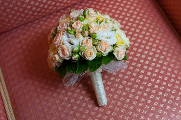 Bridal bouquet lying on a red couch