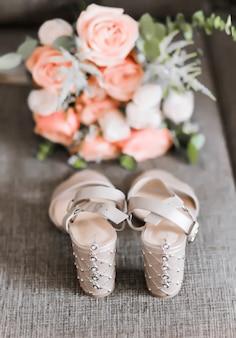 분홍색, 흰색 장미와 녹지의 신부 부케, 침대에 회색 여성 신발. 웨딩 컨셉