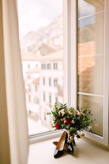 빨간색과 분홍색 장미, 회양목 가지의 신부 부케, 창가에 브로치가있는 흰색 꽃과 빨간 리본이 피고 그 근처에 검은 신부 신발이 없습니다. 고품질 사진